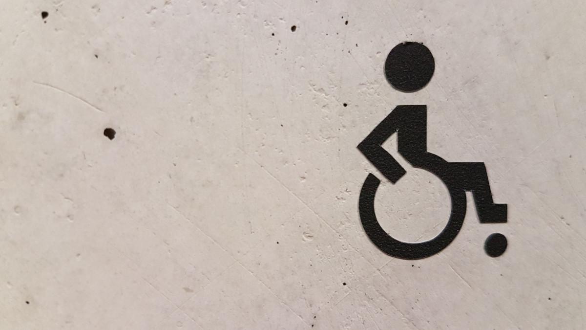 На серой стене знак человека в инвалидном кресле
