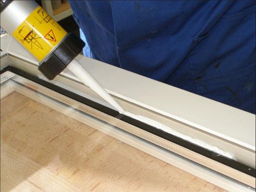 После установки стеклопакета в основание фальца вводится специальный клей Kodiglaze P с помощью клеевого пистолета